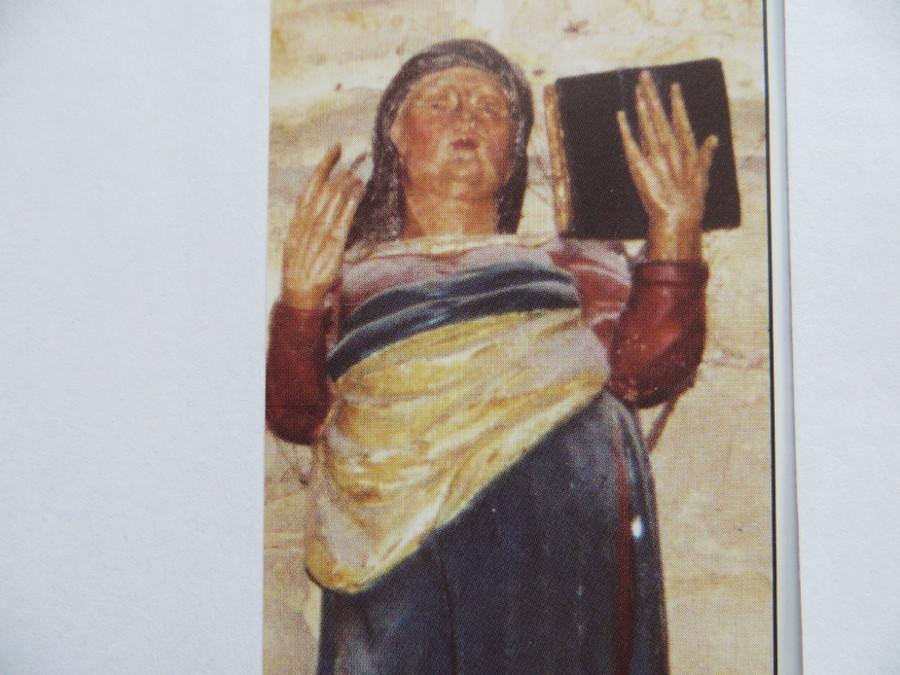 houten beeld van hilsondis, met boek in haar opgeheven handen